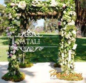 свадебная арка украшена мхом и цветами